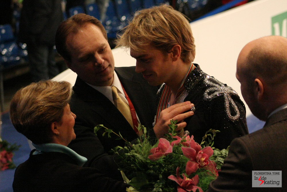 A touching moment at the end of the ice dancing event: the coach' hand on Nick' s heart