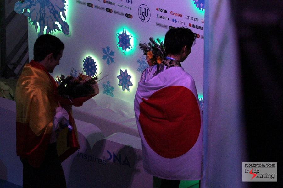With the flags on their shoulders, Yuzuru Hanyu and Javier Fernandez leave the ice and enter backstage