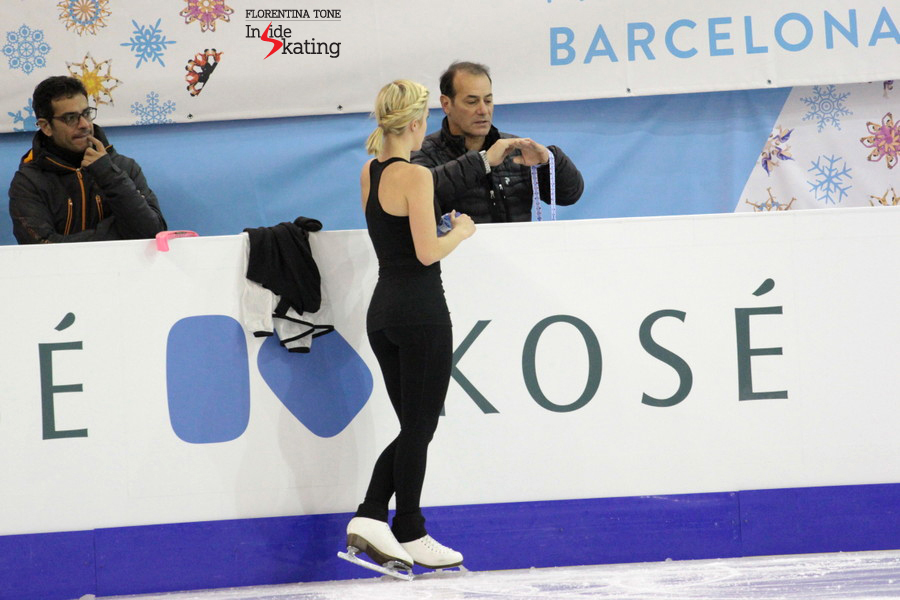 Talking to her coach, Rafael Arutyunyan, on the morning of the ladies' short program (December 11th); on the banner behind them, one can see a golden snow flake: that's Ashley at 2012 Grand Prix Final in Sochi, where she won the silver medal. Two years later, in Barcelona, she'd get the bronze.