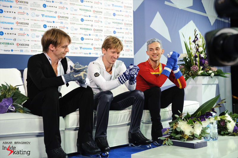 Sergei Voronov, Konstantin Menshov and Adam Rippon – and their distinctive pairs of mittens – after the medals ceremony in Espoo