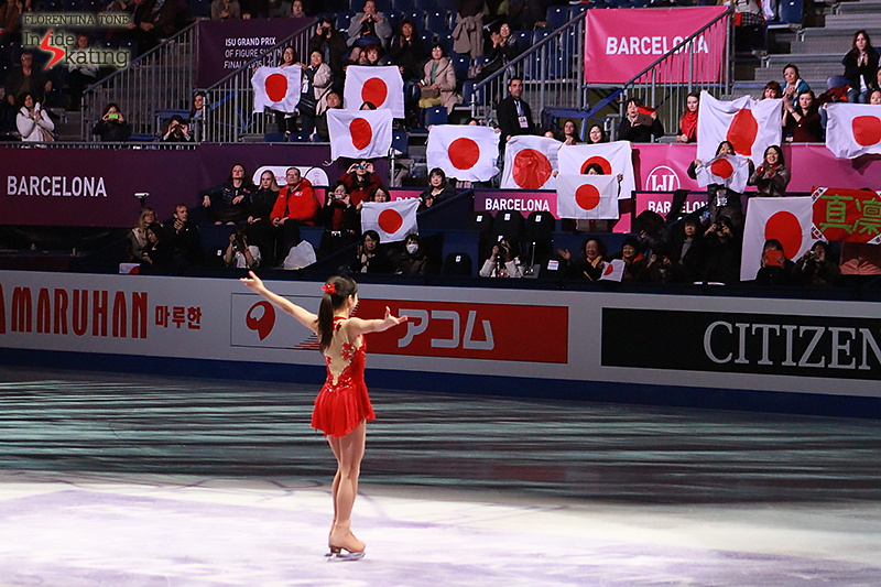 Marin Honda during the medals ceremony, as if she were embracing the audience and the red dot flags in the arena