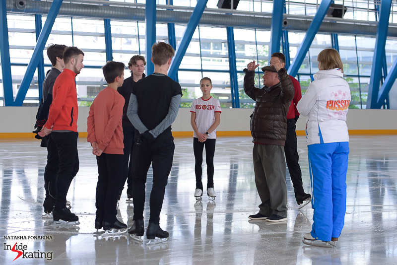 Misha Ge (in red), at Alexei Mishin's skating school in Saint Petersburg, in August – coach Mishin gives instructions, and everyone listens carefully. Among those photographed, Elizaveta Nugumanova, Alexander Petrov, Petr Gummenik, Artur Dmitriev, and even Elizaveta Tuktamysheva is in the group, though you can only see a part of her white skating boot and a glimpse of her ponytail...