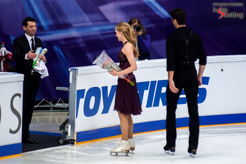 A smiling Nikolai Morozov waiting for Kaitlyn and Andrew at the boards, at the end of their free dance in Moscow