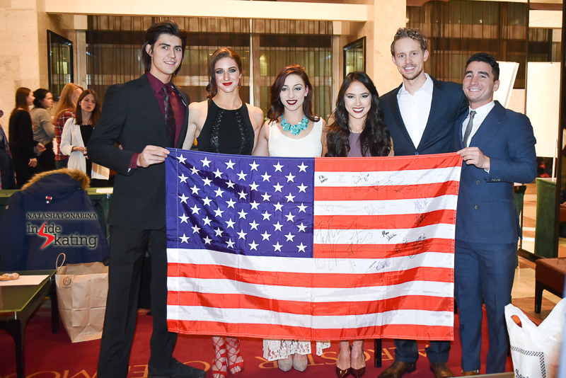 Team USA, holding a flag and smiling for the cameras: Alex Benoit, Elliana Pogrebinsky, Courtney Hicks, Madison Chock, Evan Bates, Max Aaron