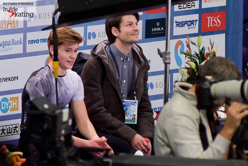Skater and coach sitting in the Kiss and Cry after Deniss' short program
