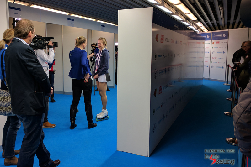 Carolina Kostner happily smiling in the mixed zone; behind the wall, a long line of journalists waiting...